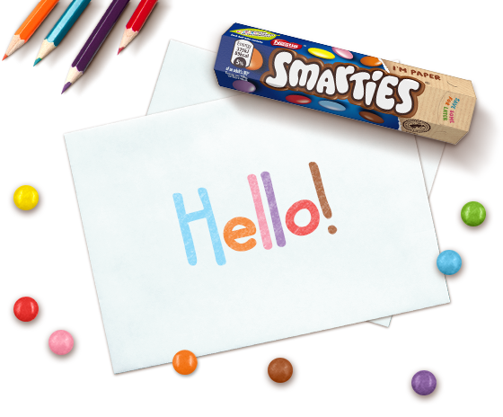 """Paper with """"hello"""" text with a Smarties tube"""